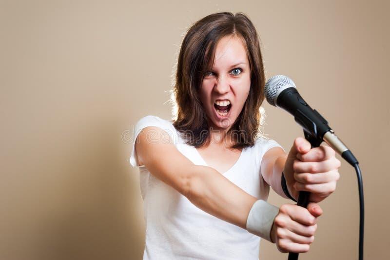 Vagga den kvinnliga vokalisten på grå bakgrund royaltyfri fotografi