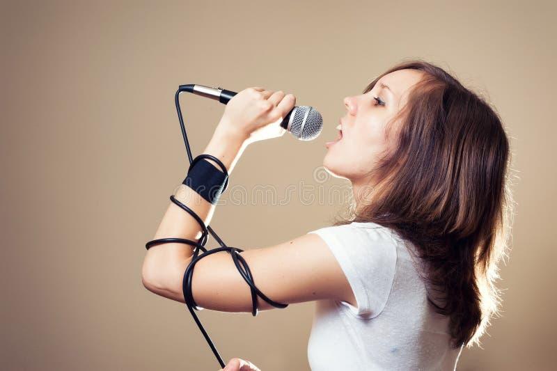 Vagga den kvinnliga vokalisten på grå bakgrund royaltyfria foton