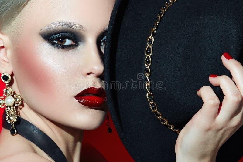 Vagga flickan i en svart hatt med röda kanter arkivfoton