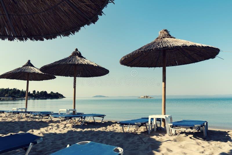 Vagga i den härliga stranden för havet nästan med sugrörparaplyer i medelhavet i Grekland royaltyfria foton