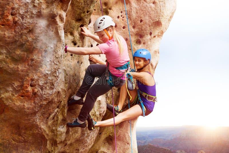 Vagga klättrare som når toppmötet av ett berg royaltyfria bilder