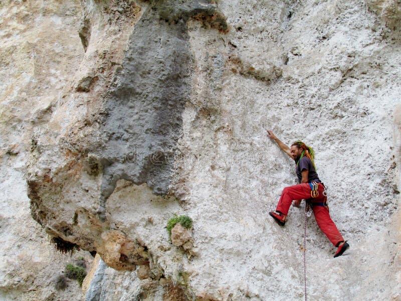 Vagga klättraren med färgrika orange och gröna dredlocks arkivfoto