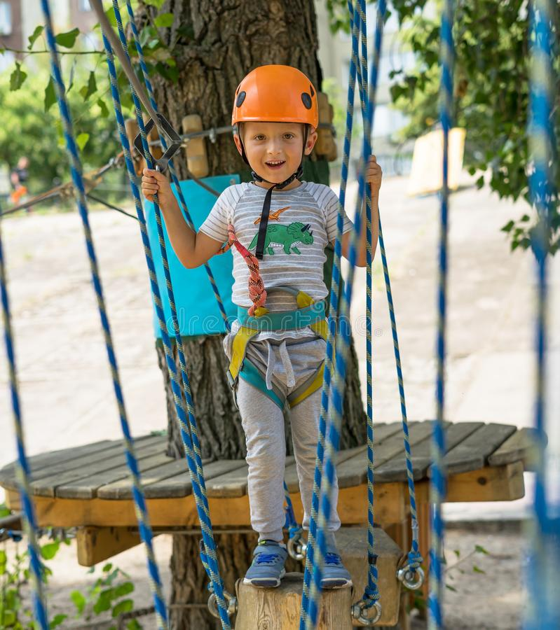 Vagga lite klättrarebandet per fnuren på ett rep En person förbereder sig för stigningen Barnet lär att binda en fnuren Kontrolle arkivfoton