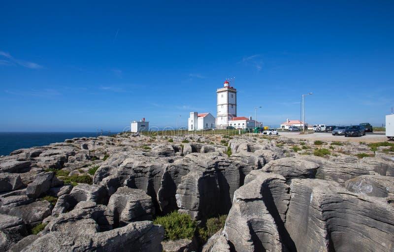 Vagga siktsbakgrund med fyren av udde Carvoeiro, Peniche, Portugal royaltyfria foton