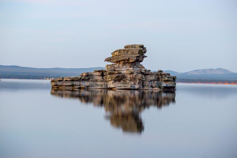 Vagga skulptur med reflexion i sjön fotografering för bildbyråer