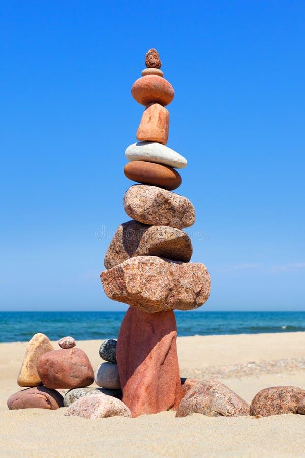 Vagga zenpyramiden av färgrika kiselstenar på bakgrunden av havet Begrepp av jämvikt, harmoni och meditationen royaltyfri fotografi