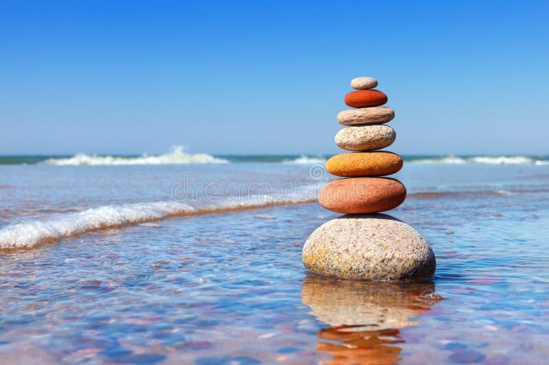 Vagga zenpyramiden av färgrika kiselstenar som står i vattnet på bakgrunden av havet Begrepp av jämvikt, harmoni och arkivbilder