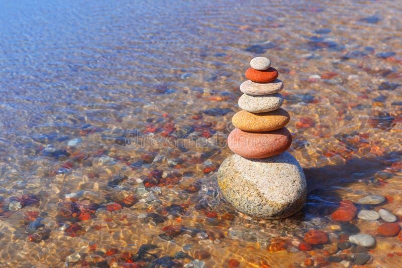 Vagga zenpyramiden av färgrika kiselstenar som står i vattnet på bakgrunden av havet Begrepp av jämvikt, harmoni och arkivbild