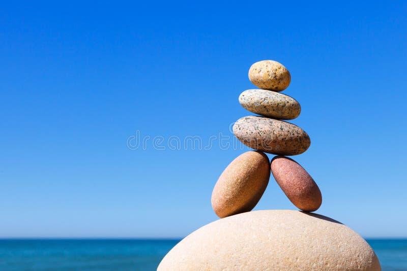 Vagga zenpyramiden av f?rgrika kiselstenar p? en strand p? bakgrunden av havet arkivfoton