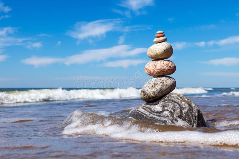 Vagga zenpyramiden av f?rgrika kiselstenar som st?r i vattnet p? bakgrunden av havet arkivfoton