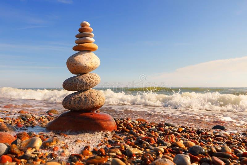 Vagga zenpyramiden av m?ng--f?rgade kiselstenar i de rosa str?larna av inst?llningssolen mot havet Begrepp av j?mvikt, harmoni oc royaltyfri fotografi