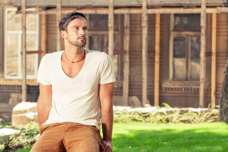 Vaggar manligt sammanträde för den unga hipsteren utanför på royaltyfri bild