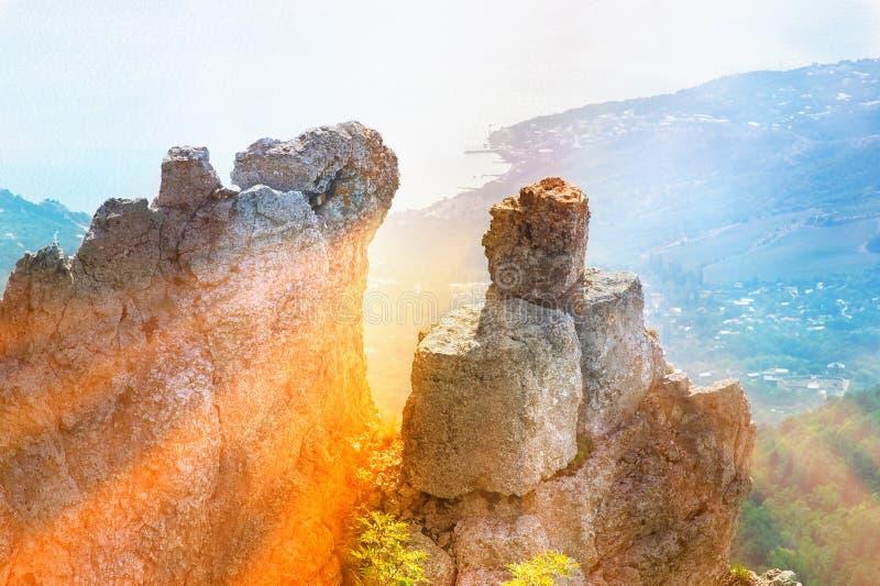 Vaggar och stenar av berget med strålar av solen och sjösidan för flyg- sikt royaltyfri foto