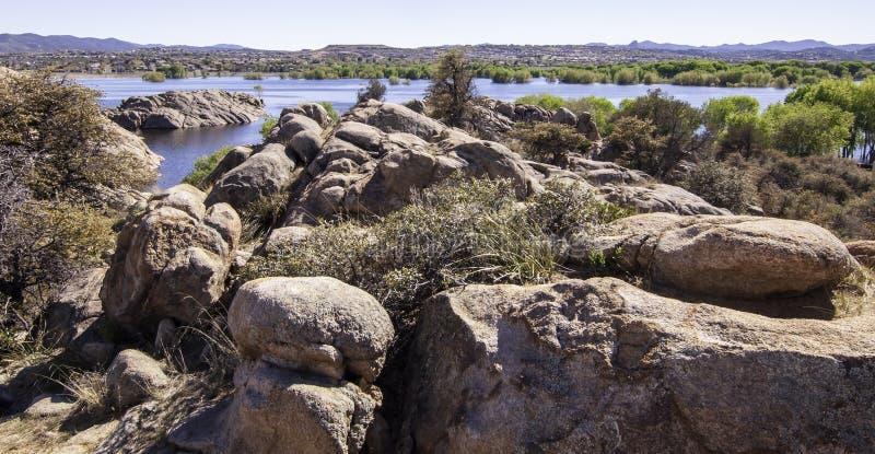 Vaggar och stenblock ovanför en sjö i Arizona, USA på en ljus vårdag arkivfoto