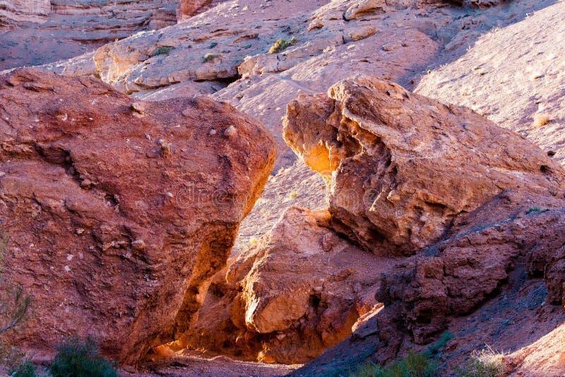 Vaggar stor sten två från det rött formen en båge och ett passerande till den Charyn kanjonen kazakhstan royaltyfri fotografi