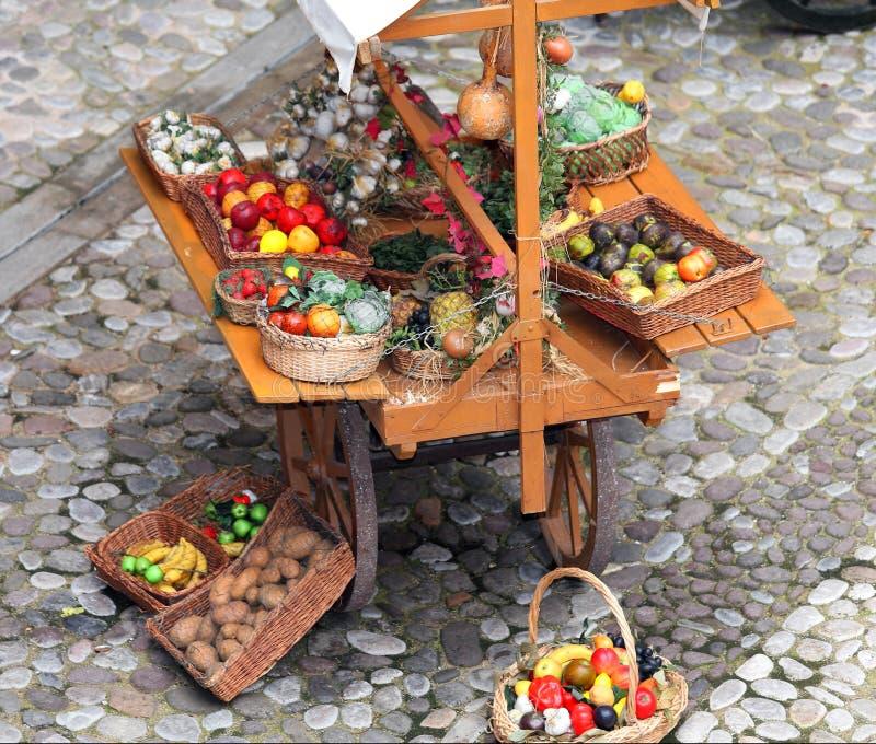 Vagn av grönsakshandlaren med frukt och grönsaker som är till salu på sten royaltyfria bilder