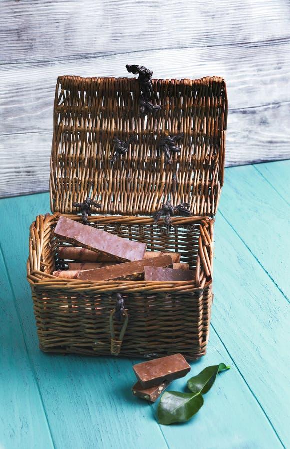 Vagn-bröstkorgen med stycken av choklad med muttrar och rånet rullar arkivfoto