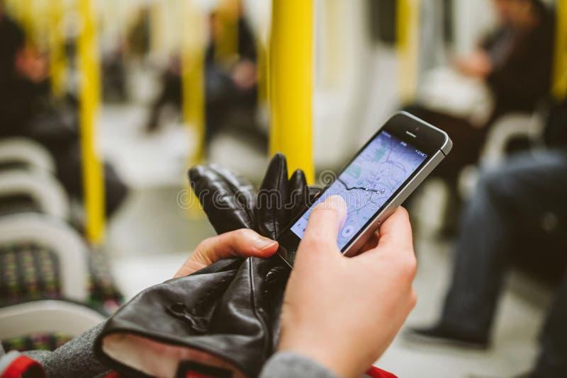 Vagn för rör för drev för kvinnainsdetunnelbana genom att använda smartphonen för att se Met arkivfoton