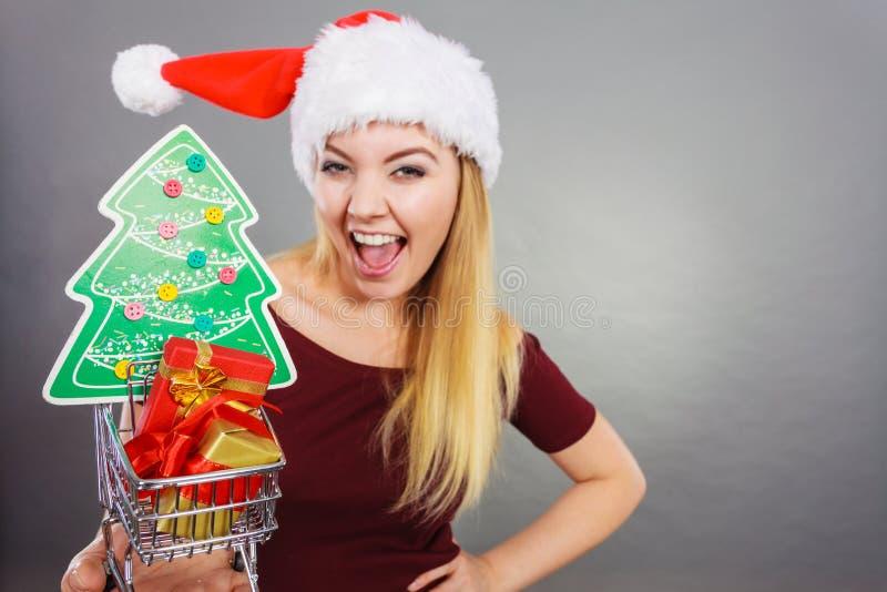 Vagn för shopping för jultomtenkvinna hållande med julgåvor arkivfoton