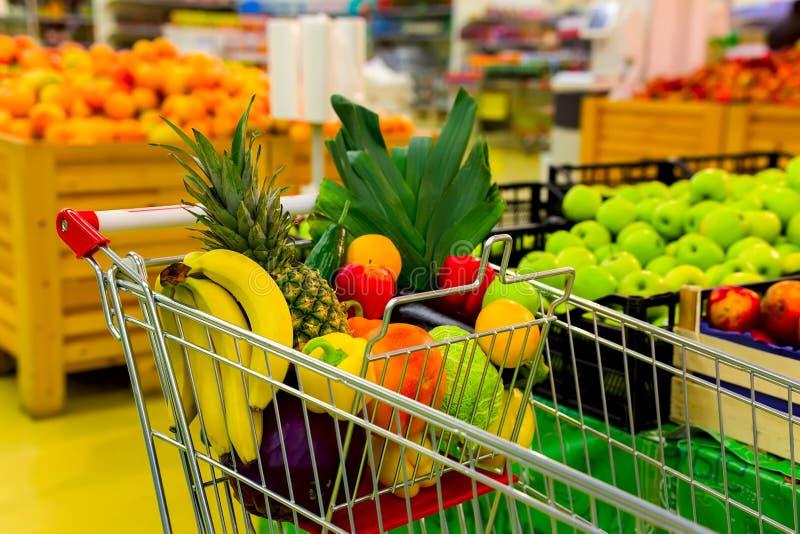 Vagn med nya frukter och grönsaker i shoppingmitt arkivfoton