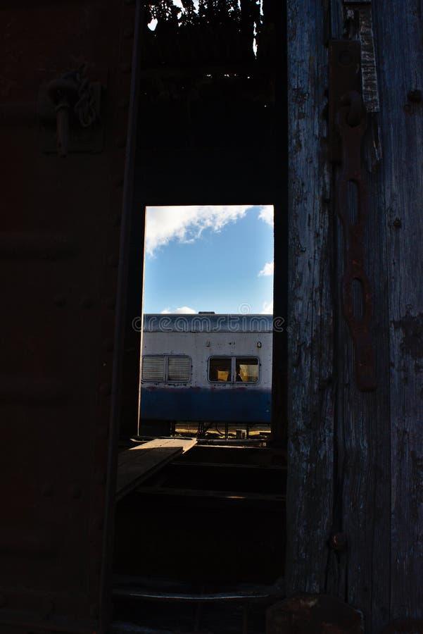 Vagnen av ett gammalt drev till och med en halvöppen dörr av en annan arkivbild