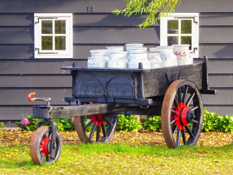Vagnen av mjölkar mycket cans i en lantgårdgård i Holland fotografering för bildbyråer