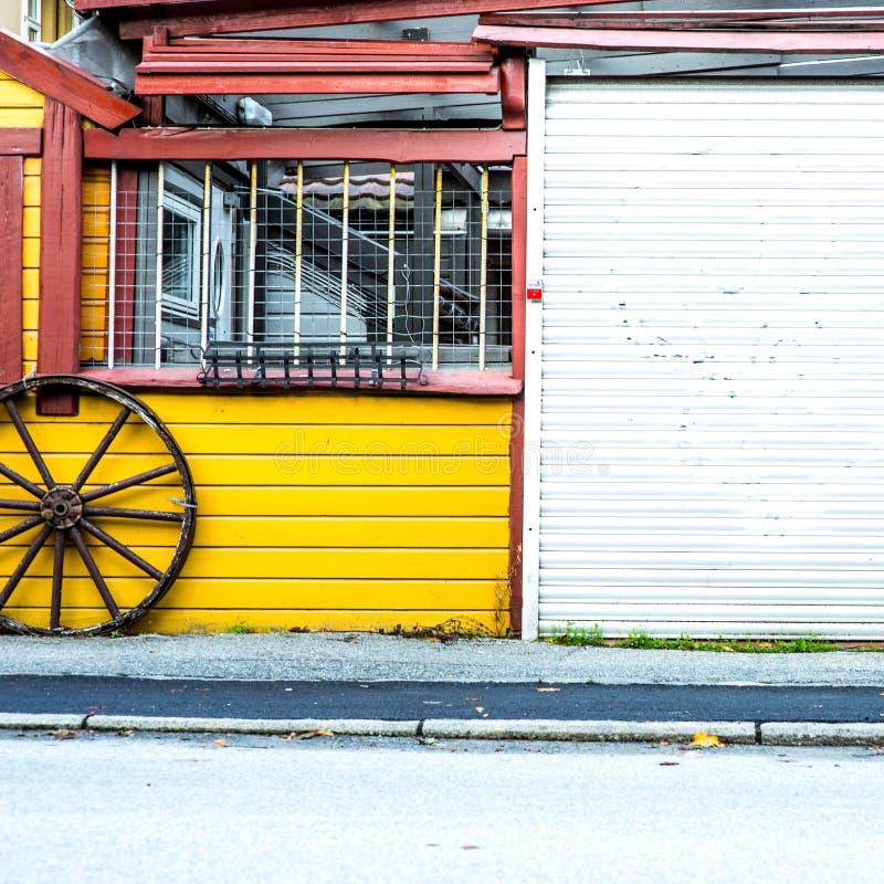 Vagnhjul som lutar på en gul träbyggnad fotografering för bildbyråer