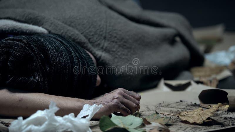 Vago cubierto con la manta que duerme en la calle del otoño, inseguridad social, ayuda foto de archivo libre de regalías