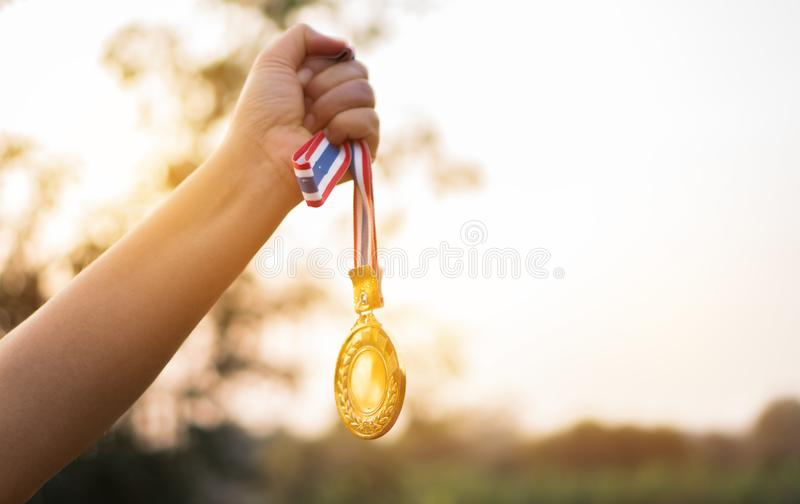 Vago delle mani della donna sollevate e tenendo le medaglie d'oro con il nastro tailandese contro il fondo del cielo blu per most fotografia stock