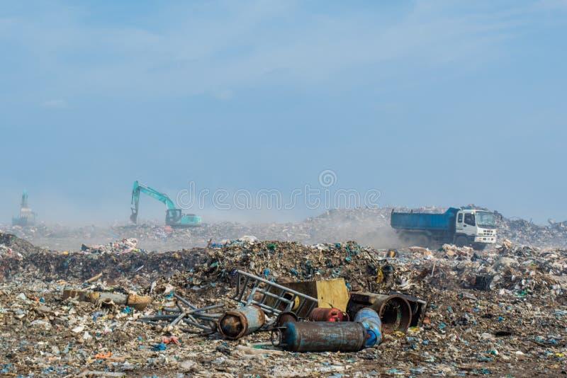 Vagone e bulldozer dell'automobile alla discarica in pieno di fumo, della lettiera, delle bottiglie di plastica, dei rifiuti e de fotografia stock