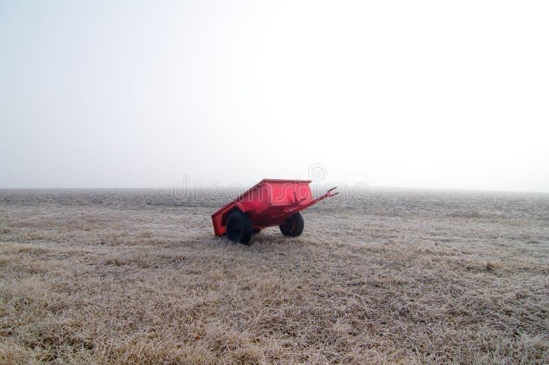Vagone e campo rossi in nebbia immagine stock