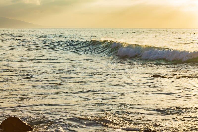 Vague de bordage formant avec casser la mousse contre l'étendue d'océan avec le ciel jaune photo libre de droits