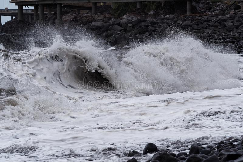 Vague de roulement sur le littoral en pierre à la tempête photos stock