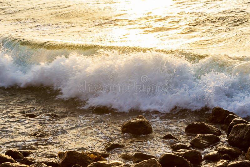 Vague se cassant sur des roches au rivage avec le lever de soleil image libre de droits