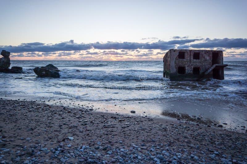 Vagues écrasant au-dessus des roches dans le coucher du soleil photos libres de droits