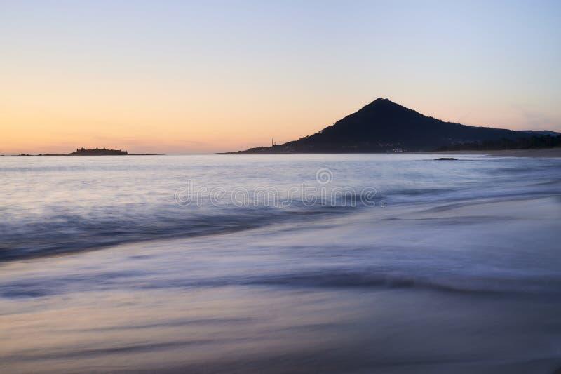 Vagues au-dessus d'une plage sablonneuse au coucher du soleil avec la montagne à l'arrière-plan images stock