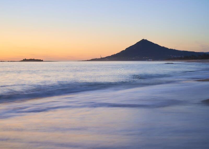 Vagues au-dessus d'une plage sablonneuse au coucher du soleil avec la montagne à l'arrière-plan image stock