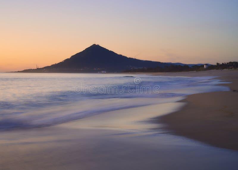 Vagues au-dessus d'une plage sablonneuse au coucher du soleil avec la montagne à l'arrière-plan photographie stock