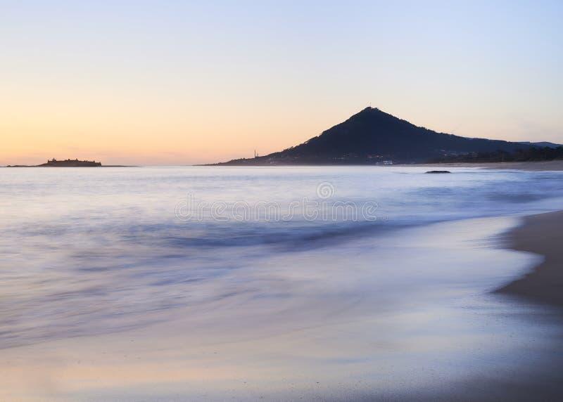 Vagues au-dessus d'une plage sablonneuse au coucher du soleil avec la montagne à l'arrière-plan photo libre de droits