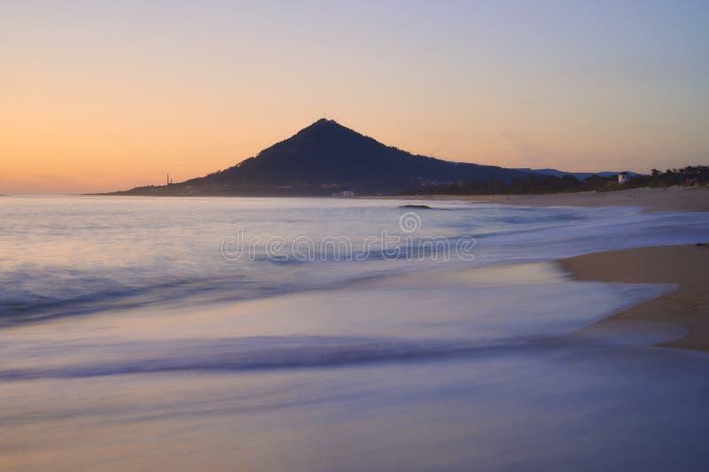 Vagues au-dessus d'une plage sablonneuse au coucher du soleil avec la montagne à l'arrière-plan photos libres de droits
