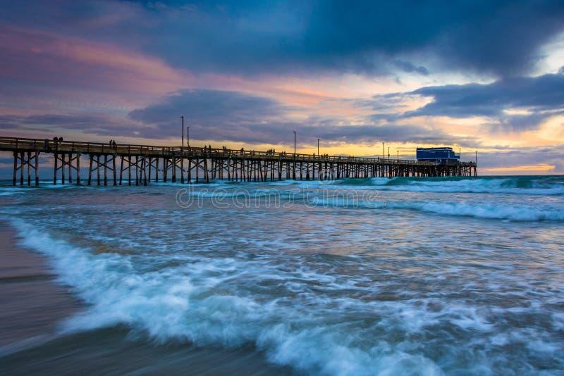 Vagues dans l'océan pacifique et le pilier de Newport au coucher du soleil images libres de droits