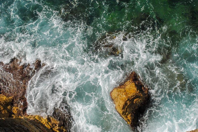 Vagues de mer éclaboussant à la nature luxuriante verte de roches entourant la belle eau de mer en île des Caraïbes de paradis photos stock