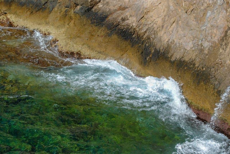 Vagues de mer éclaboussant à la nature luxuriante verte de roches entourant la belle eau de mer en île des Caraïbes de paradis photographie stock