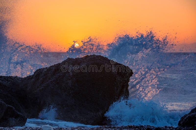 Vagues de mer écrasant et éclaboussant sur les roches sur une plage tropicale, dans la belle lumière chaude de coucher du soleil photographie stock