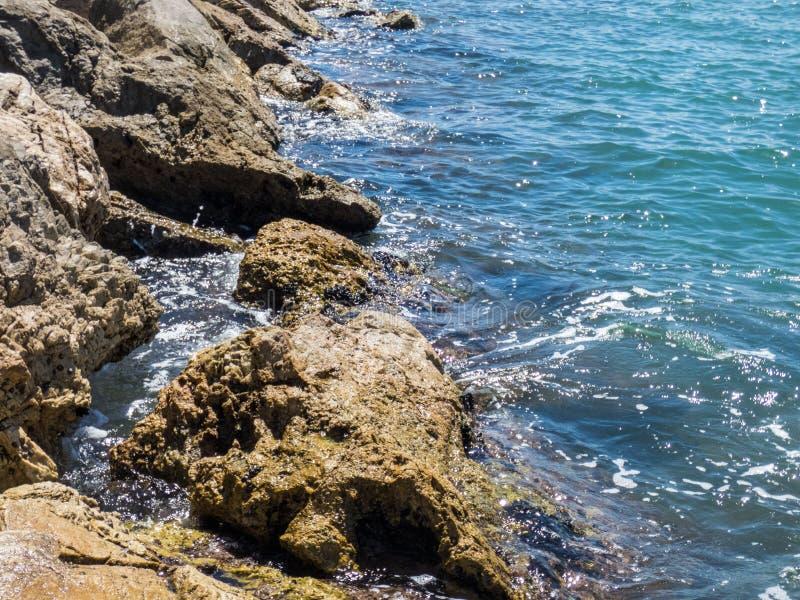 Vagues de mer frappant et éclaboussant sur quelques pierres brunes émergeant d'une eau de mer bleue photos libres de droits