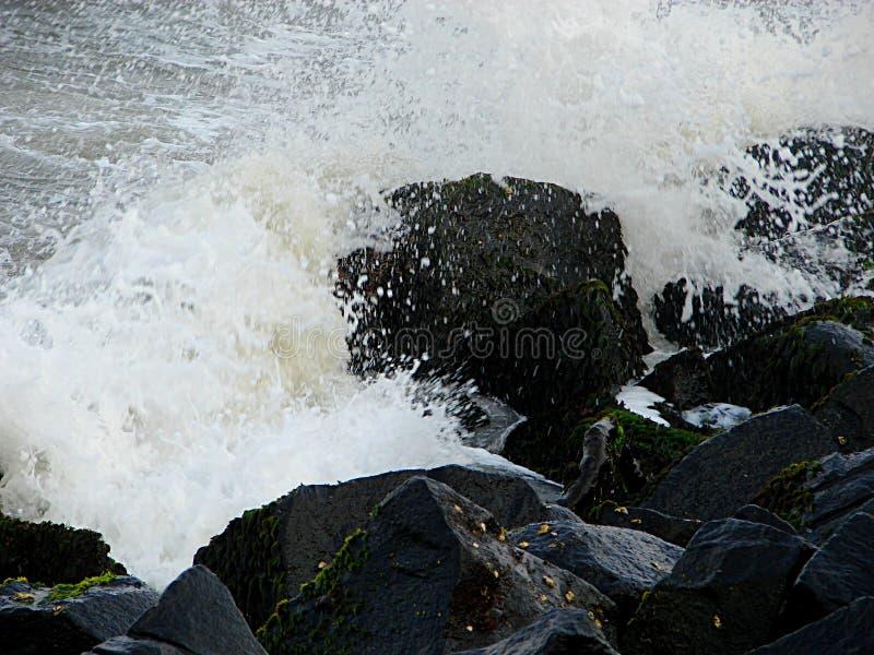 Vagues de mer se brisant sur des roches images stock
