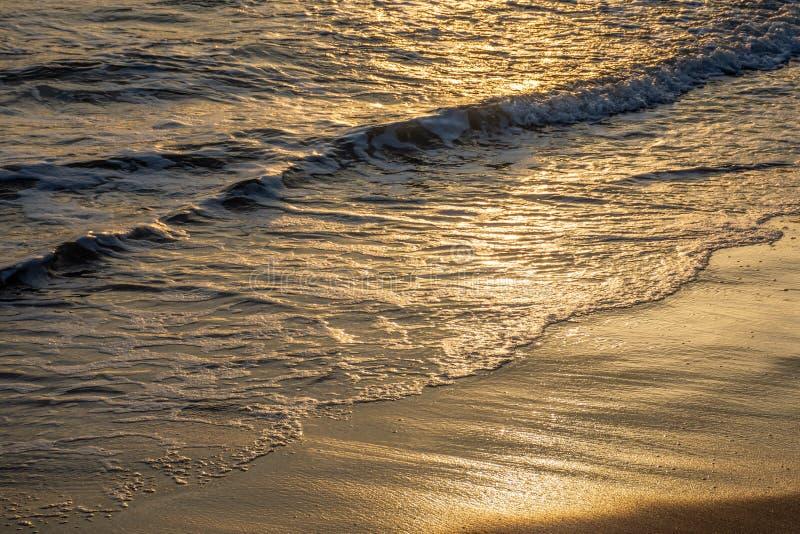 Vagues de mer sur un coucher du soleil dans la plage photographie stock libre de droits