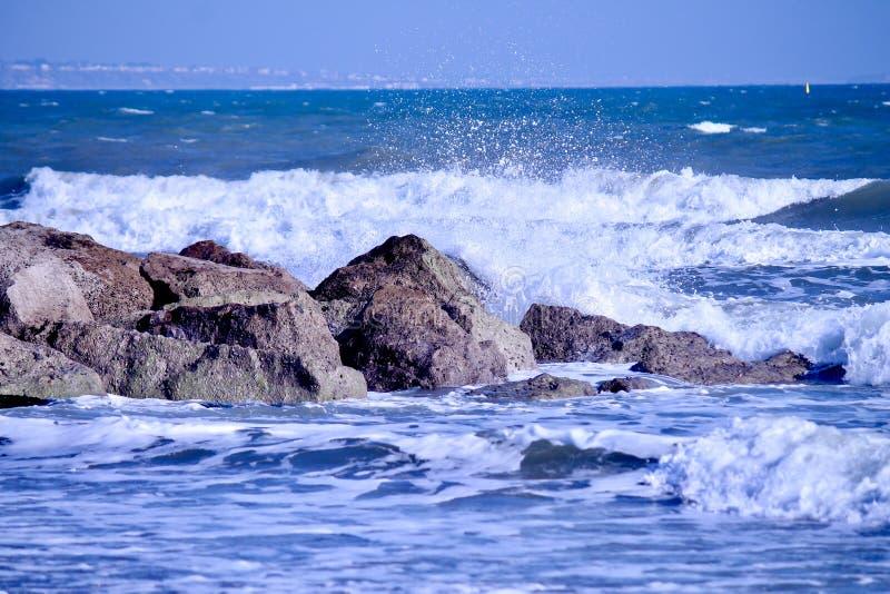 Vagues de mer venant vers des roches avec des algues photographie stock