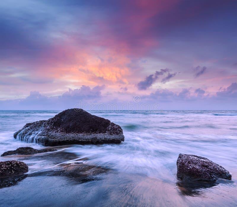 Vagues et roches sur la plage du coucher du soleil photo libre de droits