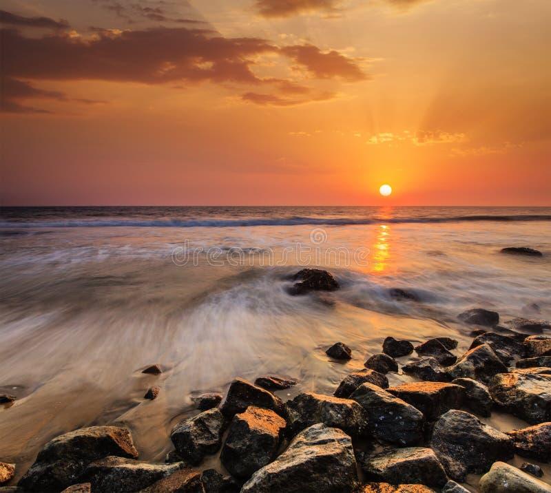 Vagues et roches sur la plage du coucher du soleil photos libres de droits